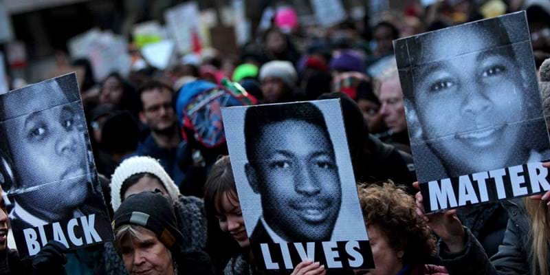 Protesters hold images of Michael Brown, Eric Garner, and Tamir Rice. 2014, Photo Credit: Yana Paskova, The New York Times (c) The New York Times