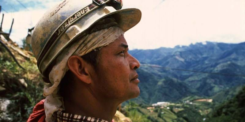 Indigenous person looking at mountains in distance, image from documentary film Marmato. This image is not available under the 4.0 Creative Commons license.