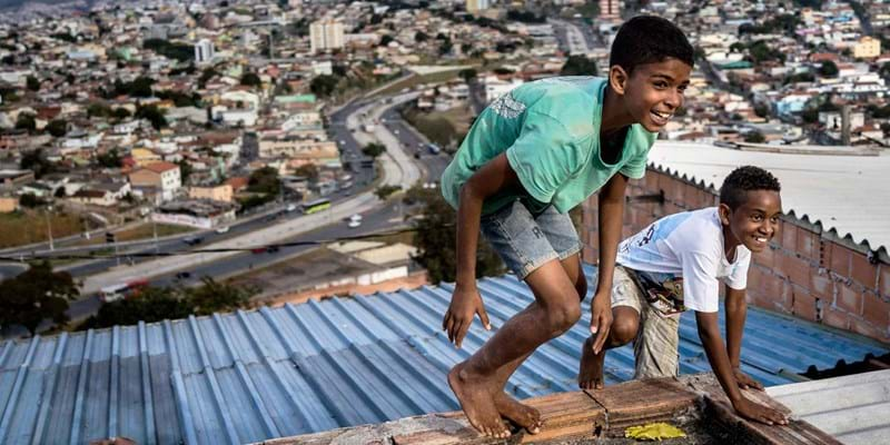 Boys playing on roofs of favela. Photo Credit: Zachary Canepari. (c) Panos Pictures.
