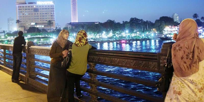 Egyptians walking on a promenade overlooking the Nile in downtown Cairo.