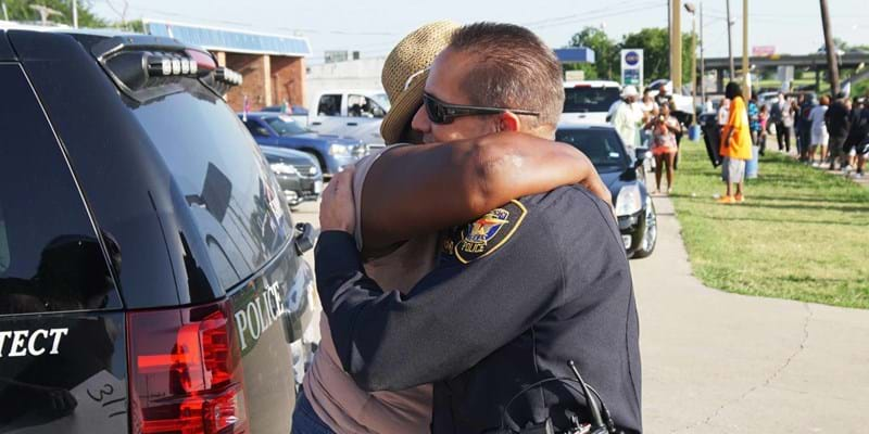 Citizens and policeman hug in reaction to Dallas shootings. Dallas, Texas. 2016. Photo credit: Lawrence Jenkins