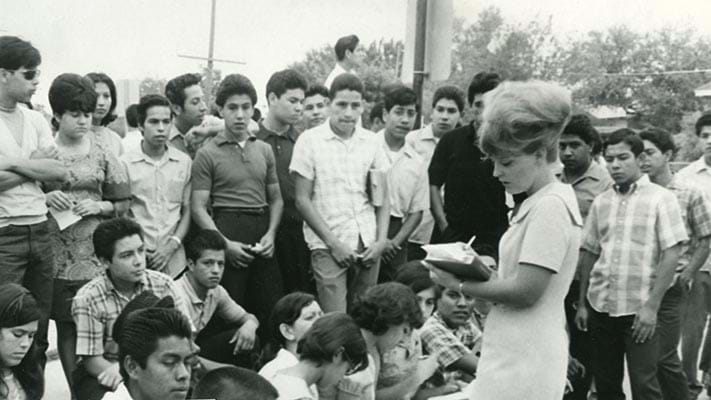 Jane Hilgen teaching her English class on the curbstone in front of the Edgewood High School after being suspended from her job as a result of her activities during a student walk out in San Antonio, Texas. 1968. Photo Credit: © Ford Foundation