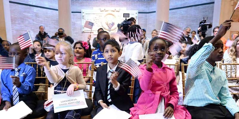 Children wave American flags after taking the Oath of Allegiance as they become U.S. citizens. Credit: Anthony Behar/Sipa USA