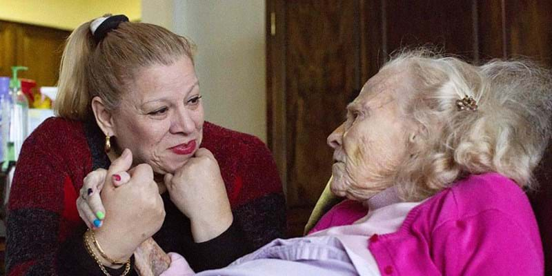 Caregiver Vilma holds older woman's hand.