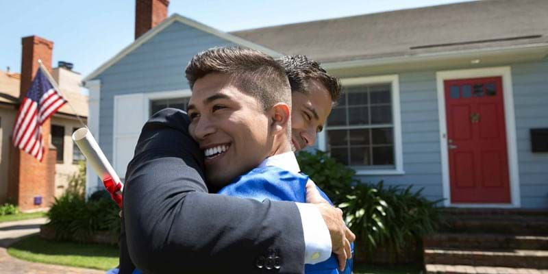Hispanic father is hugging and congratulating his graduating son.