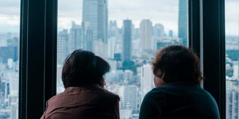 Women are looking out of a hi-rise building window.