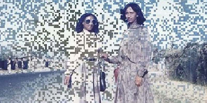 Two women standing against a glitchy background