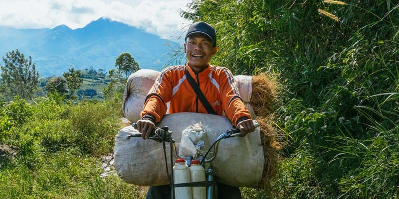 Young man on a moped transporting Vetiver. Sukamukti, Indonesia. photo credit Fitria Rifki