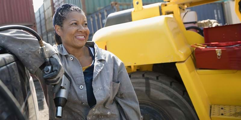 A female African American mechanic holds a drill, fixing machinery in industrial container yard.