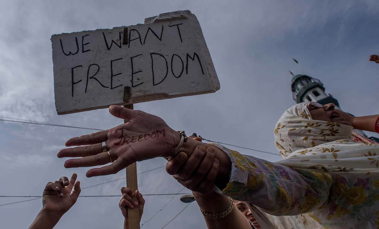 "Women protesters in India are holding a sign that reads ""We want freedom"" and a woman with the word ""freedom"" written on her hand."