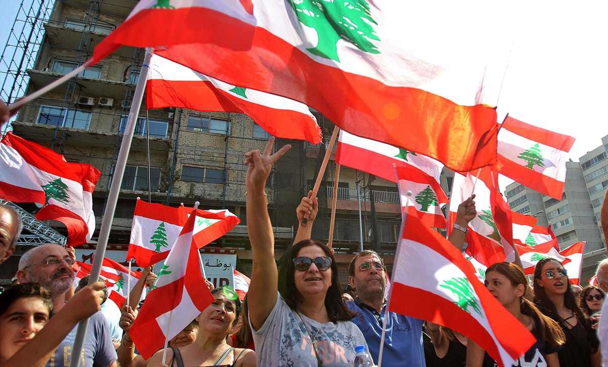 Lebanese demonstrators raise national flags in protests against a proposed tax on mobile messaging applications.