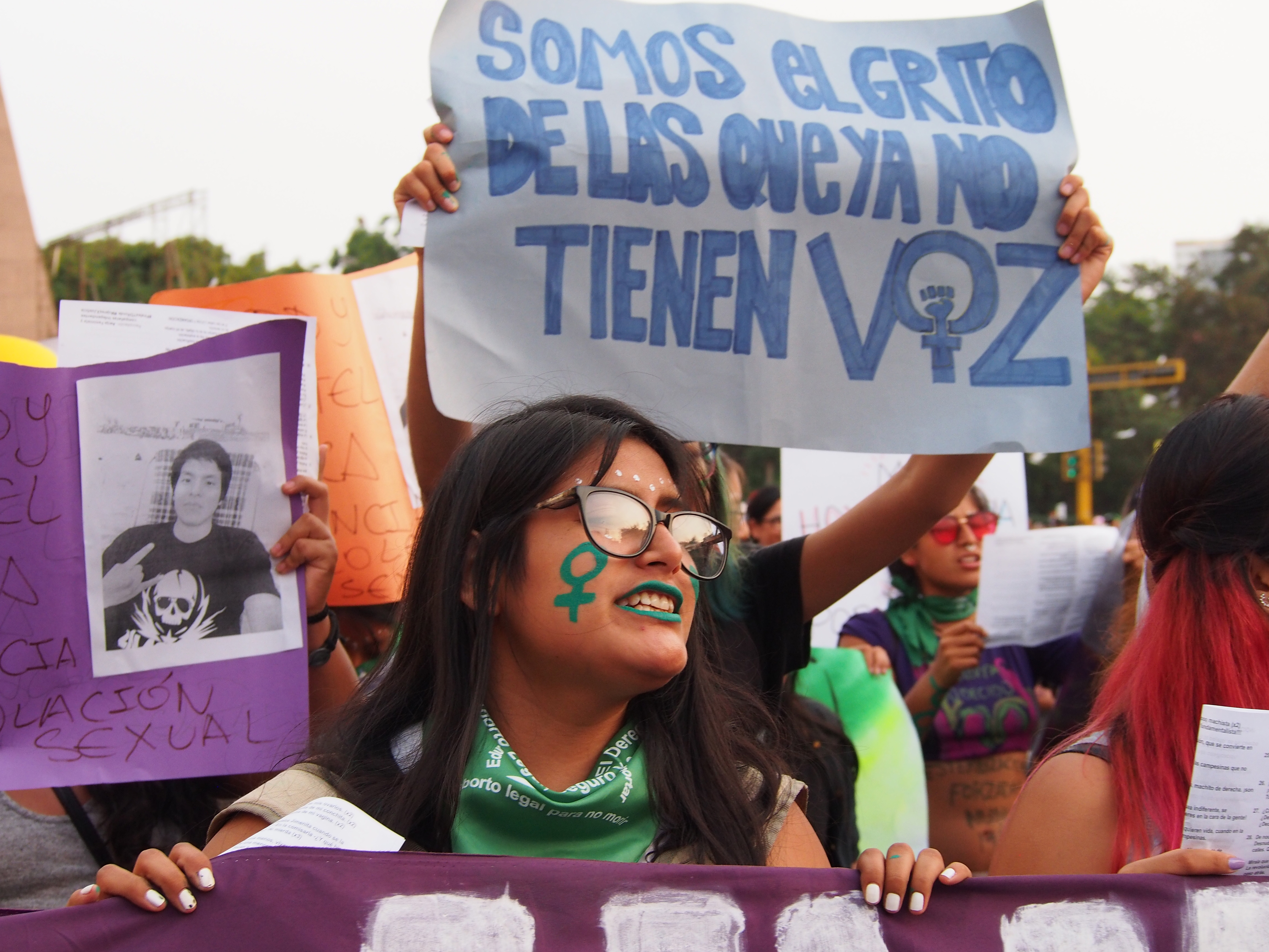 A girl with a green feminist symbol painted on her face when thousands of women from feminist and sympathetic groups take to the streets in Lima, Peru