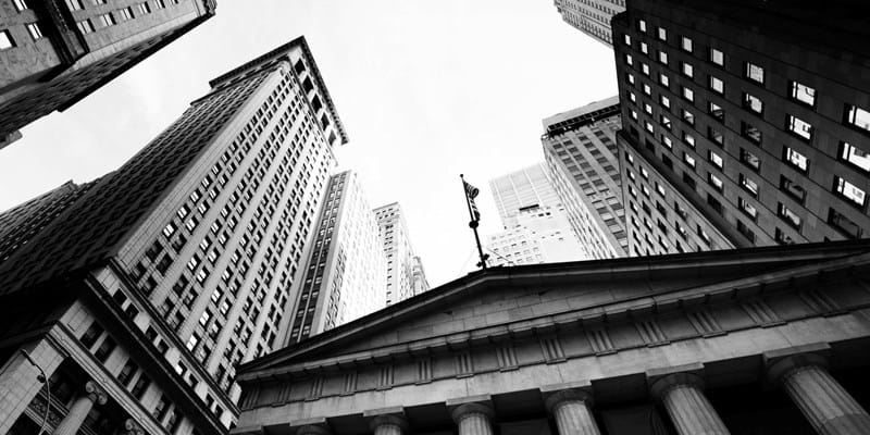 A black and white photo taken in front of Federal Hall, NYC is angled up to capture the top of the building and surrounding offices. Photo by: Lisa-Blue