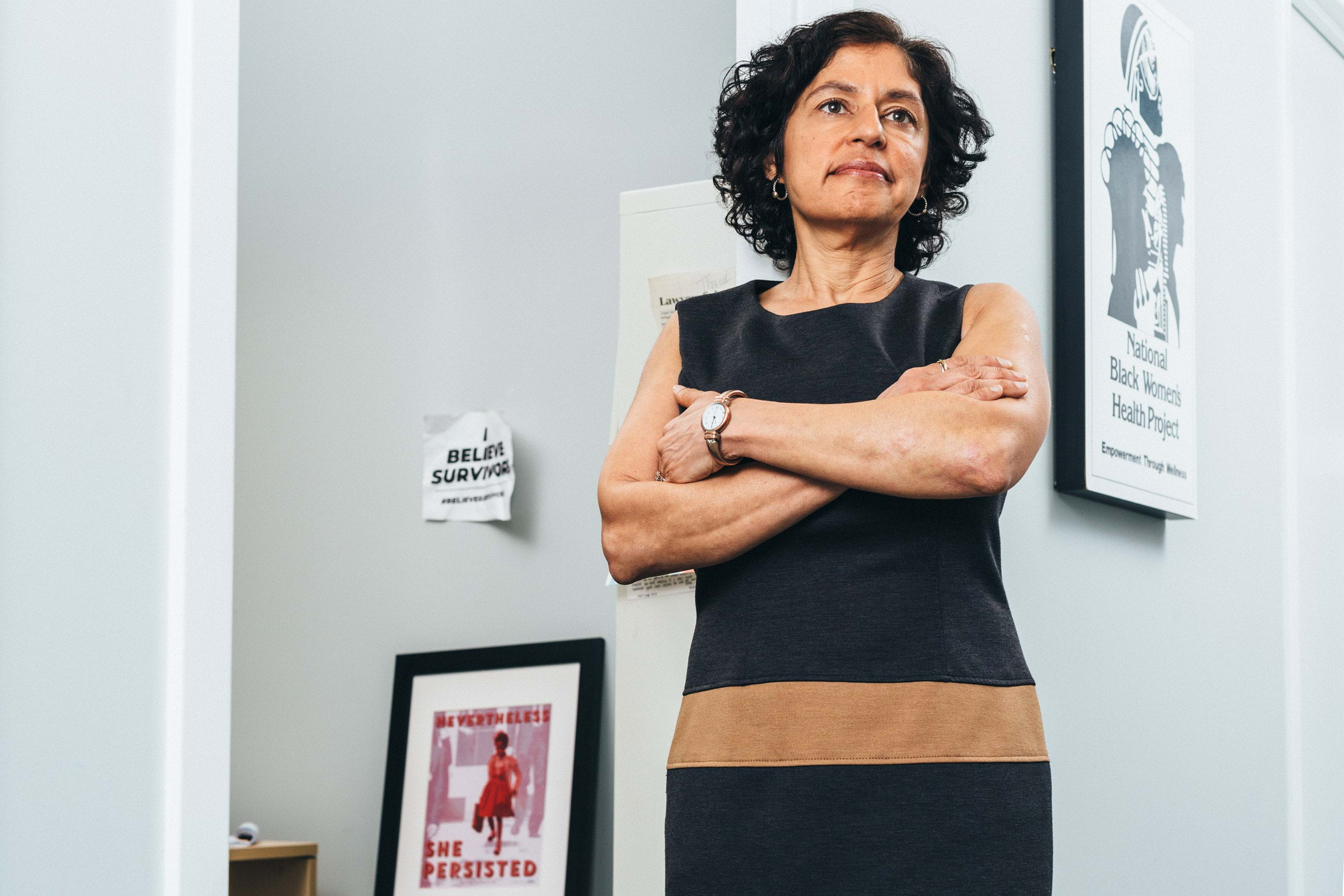 Sharyn Tejani, Director of the TIME'S UP Legal Defense Fund, standing with her arms crossed in her office.