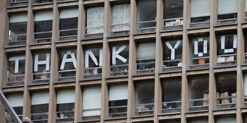 """Thank you!"" spelled out with sheets of paper taped to the windows of an NYC building."