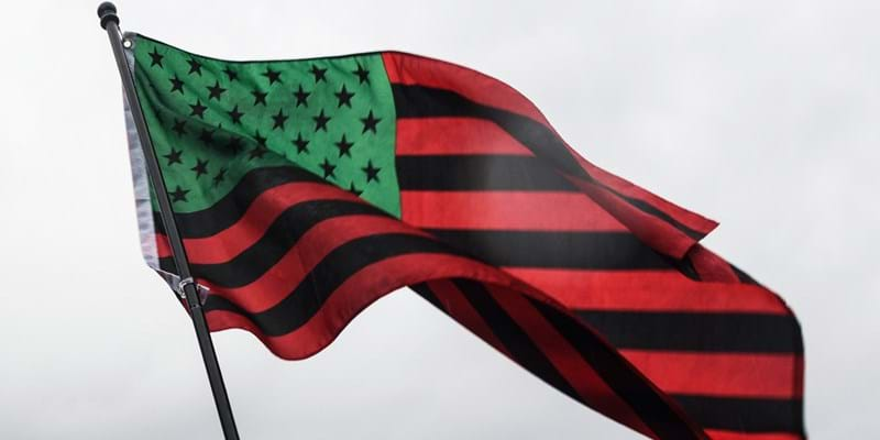 The African American flag, an American flag recolored with red, black, and green, blows in the wind.
