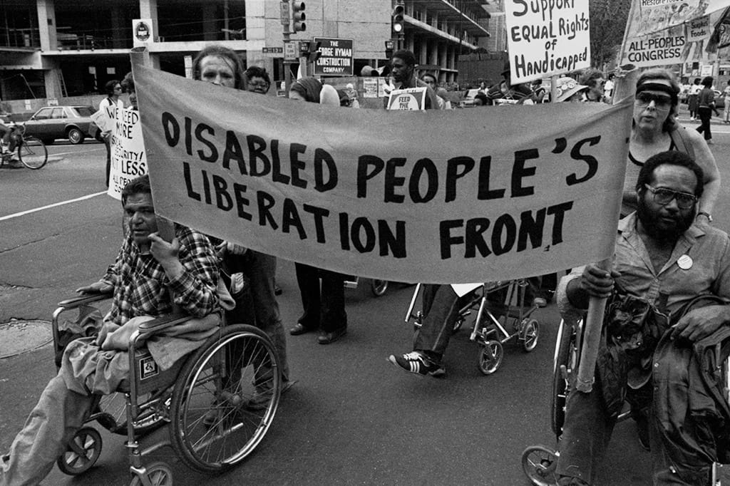 "Two people in wheelchairs lead a protest with a banner that reads ""Disabled People's Liberation Front"" with a crowd behind them."