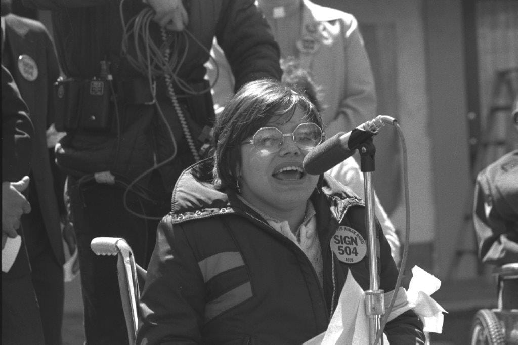 Judy Heumann in a wheelchair speaking into a microphone. She is wearing glasses and a coat with a Sign 504 sticker.