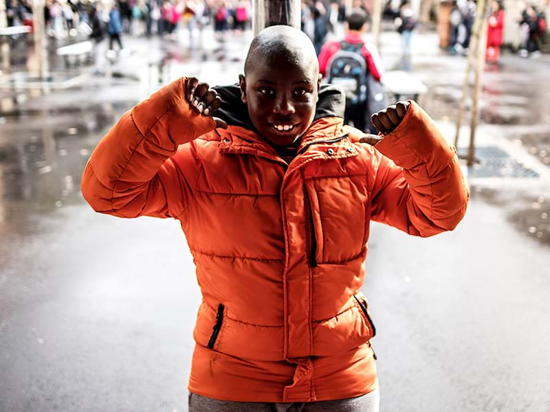 A young black boy with autism smiles with his arms raised in the schoolyard. He is wearing a bright orange puffy coat.