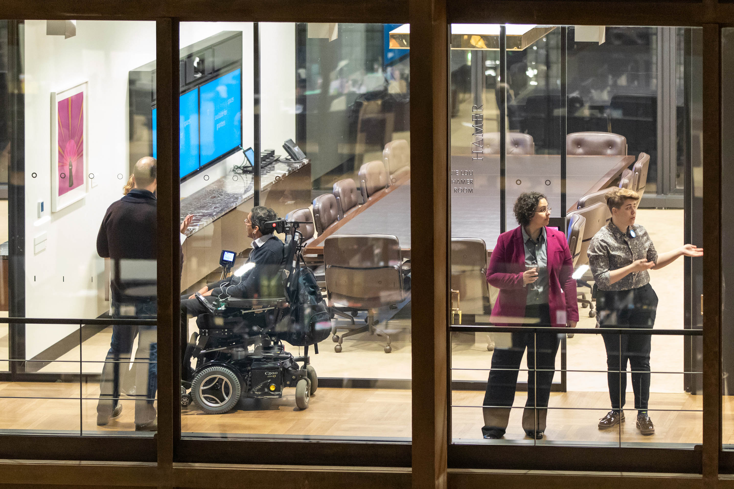 Ford staff giving visitors a tour of the glass and steel lined headquarters. On the left, a man in a power wheelchair talks with two standing people while two people stand on right looking down the hallway.