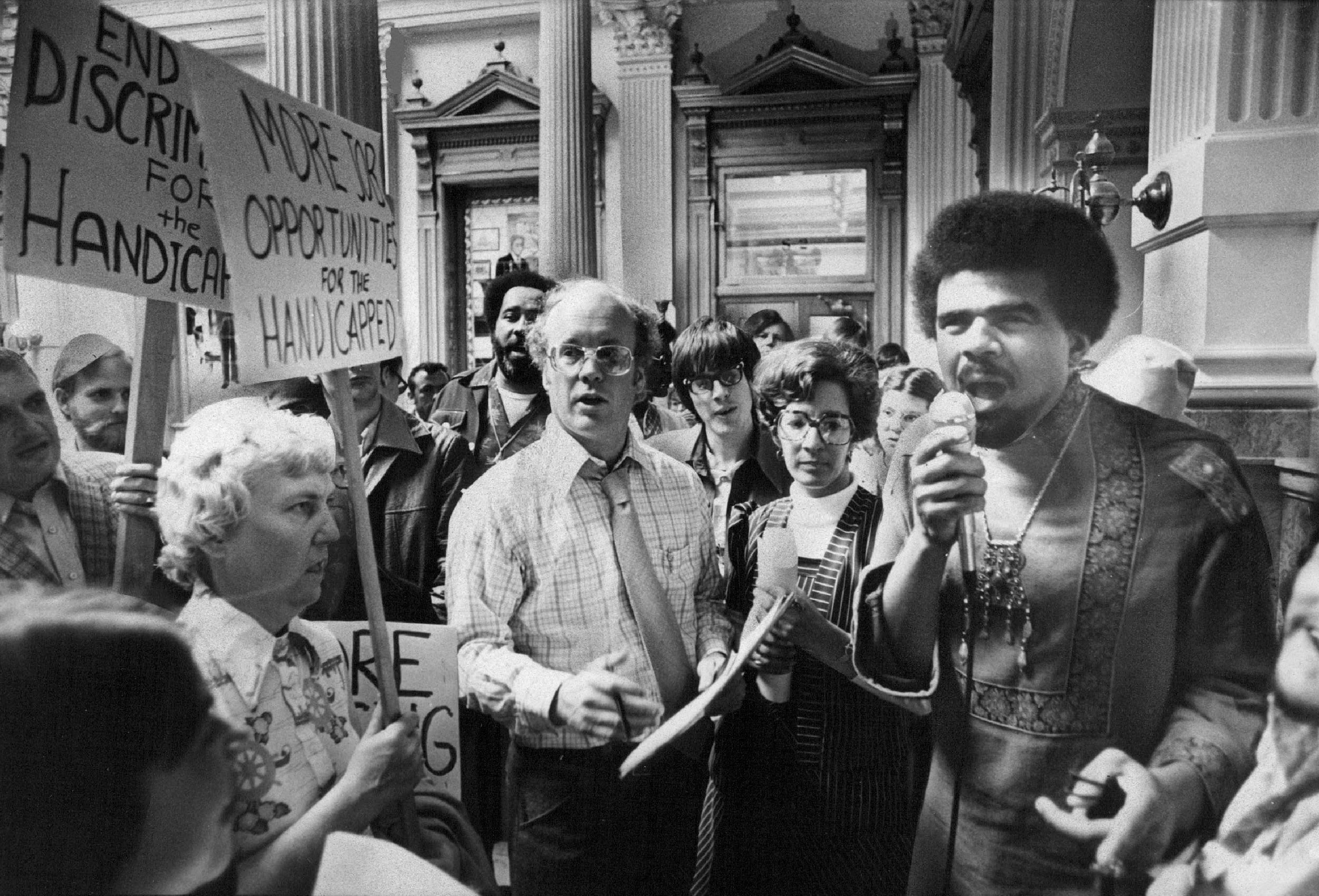 In a vintage photograph, a Black man speaks passionately into a microphone at a rally for disability rights as people around him hold signs demanding equal opportunities and an end to discrimination.