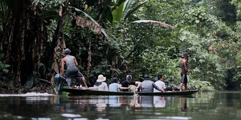 A man powers a canoe with a delegation from Ford indigenous grantee AMAN while a local guide stands at the front and looks ahead in a dense forest. Photo by Kynan Tegar