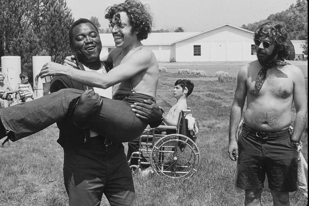 B&W photo of a Crip Camp counselor carrying one of the campers as another counselor looks on.