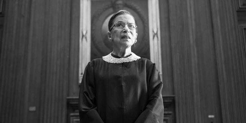 Ruth Bader Ginsburg in black judicial robe looks ahead at the bench inside the wood-paneled U.S. Supreme Court building in Washington D.C. Photo by Nikki Kahn/The Washington Post via Getty Images
