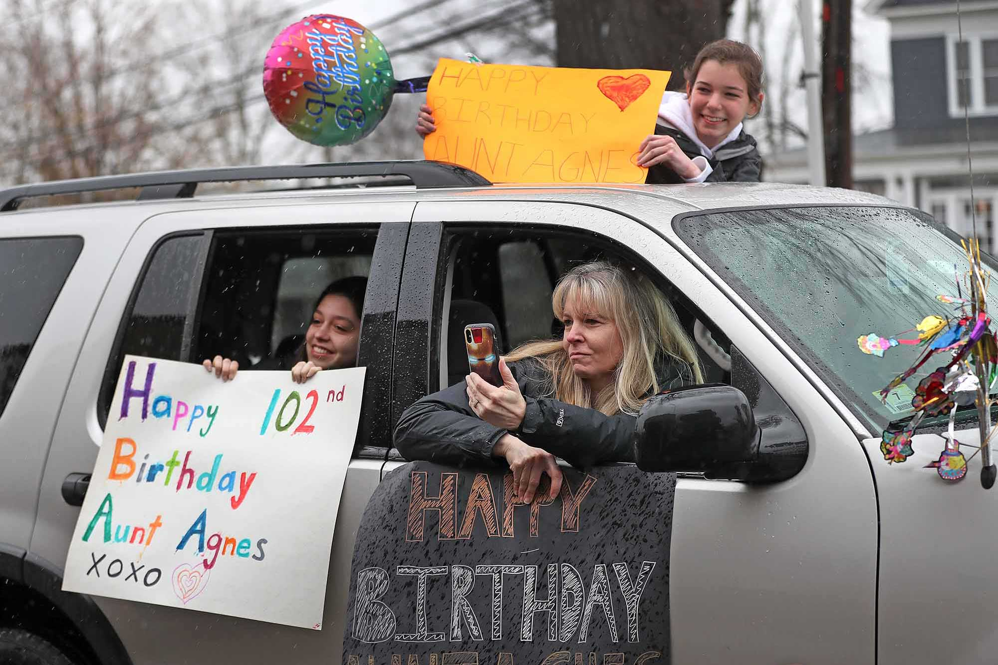 Three people hold colorful birthday signs outside of a car window.