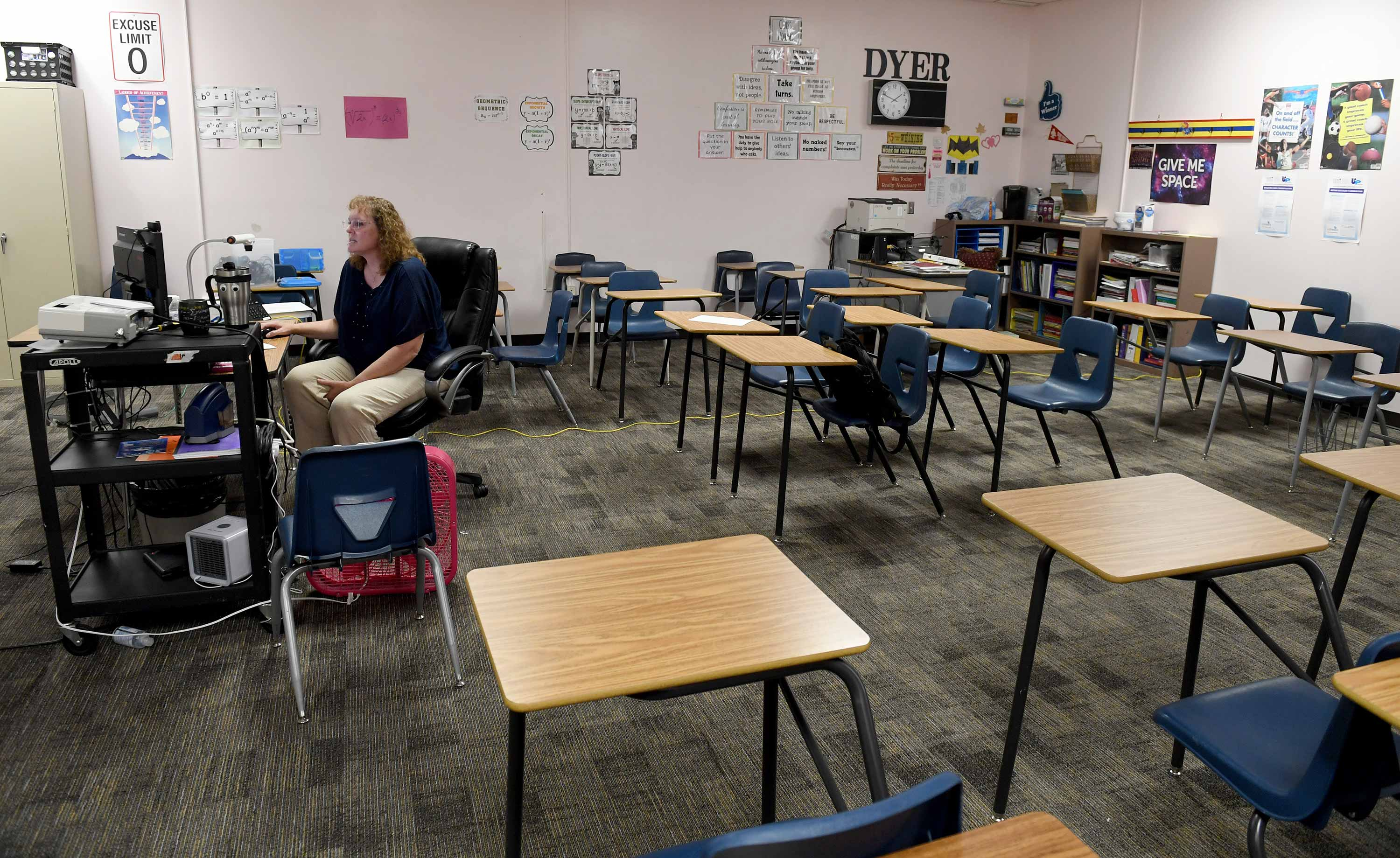 A lone teacher faces a computer screen in an empty classroom full of nearly arranged desks.