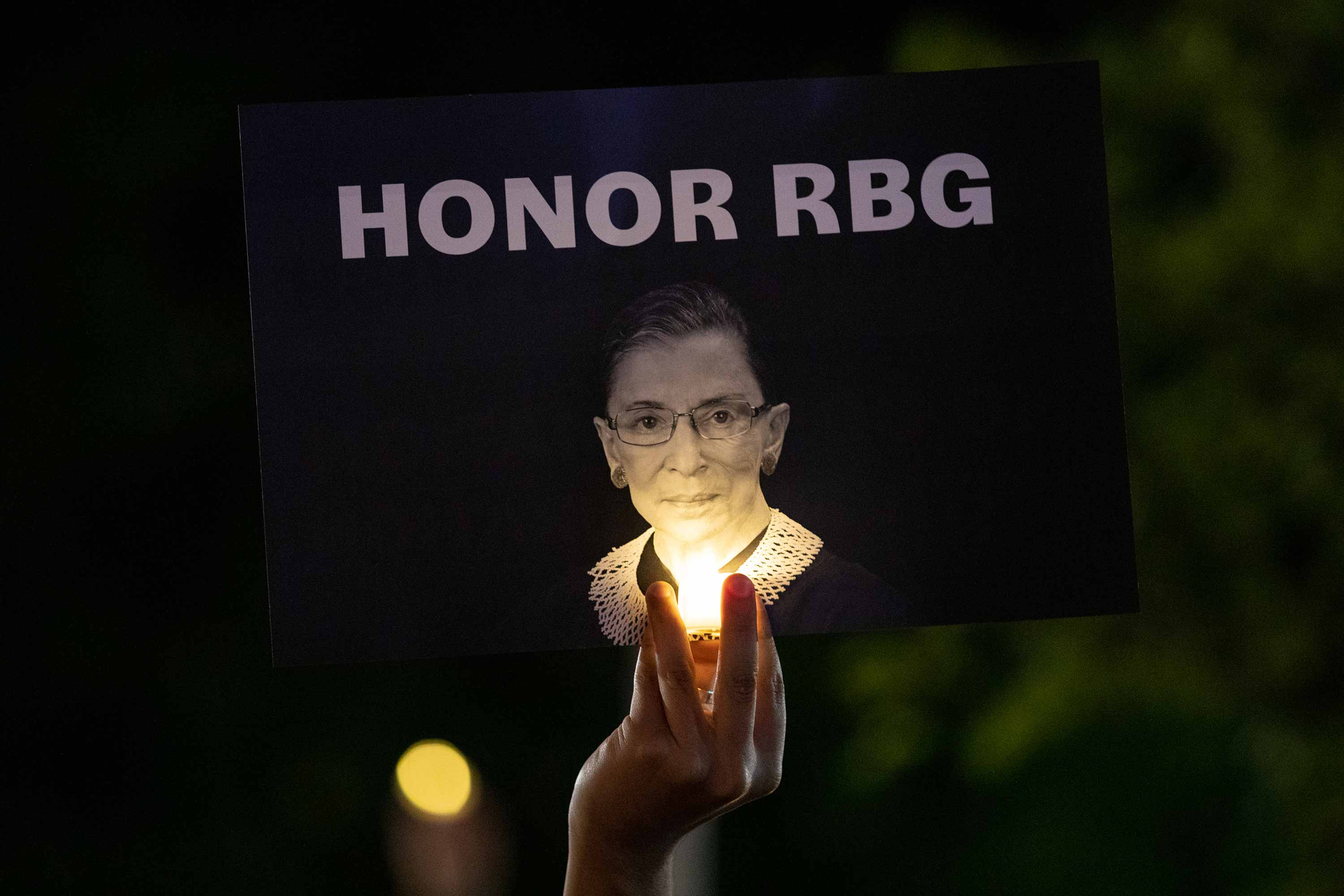 "A hand holds up a sign that reads ""Honor RBG"" while lit by a small handheld light."