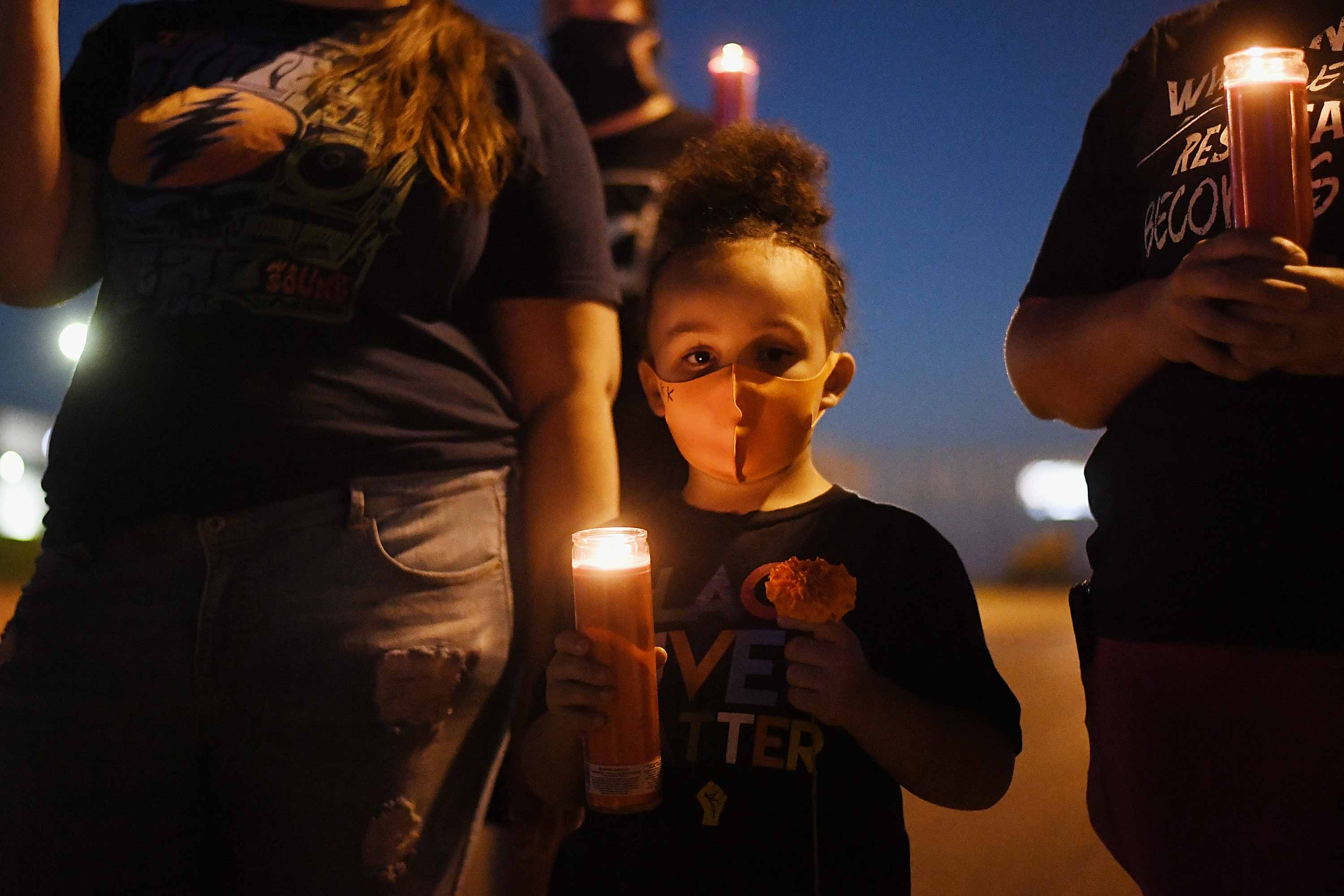 A young Black girl wearing a protective mask holds a candle in her hand while surrounded by adults.