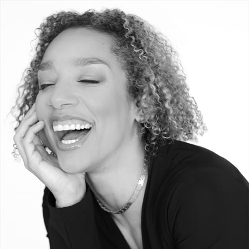 A Black woman leans forward and smiles brightly, teeth showing and eyes closed, as she rests her chin in her palm. She has light brown skin, curly shoulder-length hair with subtle highlights, and wears a black blouse and sleek gold necklace.