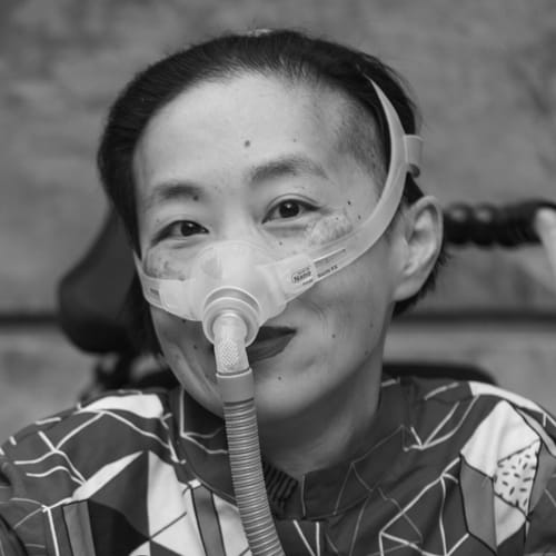 A Chinese-American woman wearing lipstick and a translucent mask over her nose and attached to a tube smiles warmly at the camera. She has cool light skin, short black hair, wears a dark shirt with a geometric pattern, and folds her hands on the control panel of her power chair.