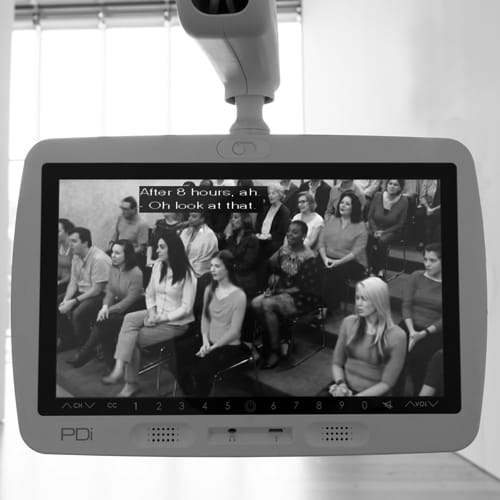 "A smooth, white television monitor attached to a robotic arm extends into an empty art gallery and plays a daytime talk show. Caption reads: ""After 8 hours, ah"" and ""Oh look at that."""