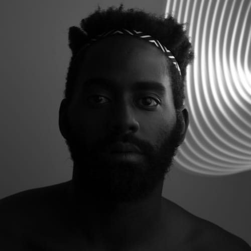 Bathed in light, a shirtless bearded Black man with dark brown skin, a short hi-top fade, and a patterned headband gazes intently into the camera.