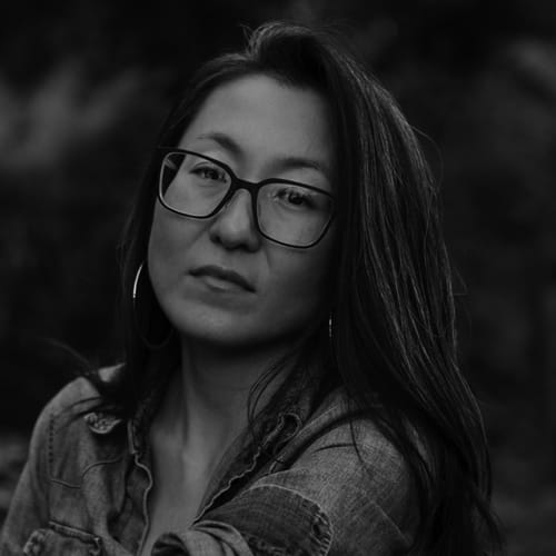 A Korean woman with warm light skin, long dark hair, big square glasses, and wearing a denim shirt sits casually outside in a wooden chair backdropped by foliage and stares confidently into the camera.