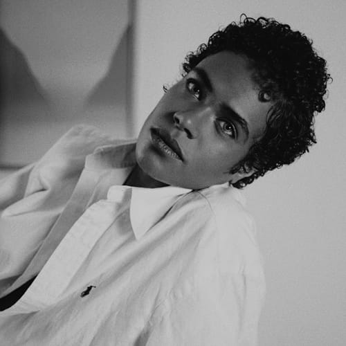 Leaning back casually with a serene expression, a Black nonbinary trans person with medium brown skin, and short curly black hair gazes into the camera. He has a defined brow and wears an unbuttoned white shirt.