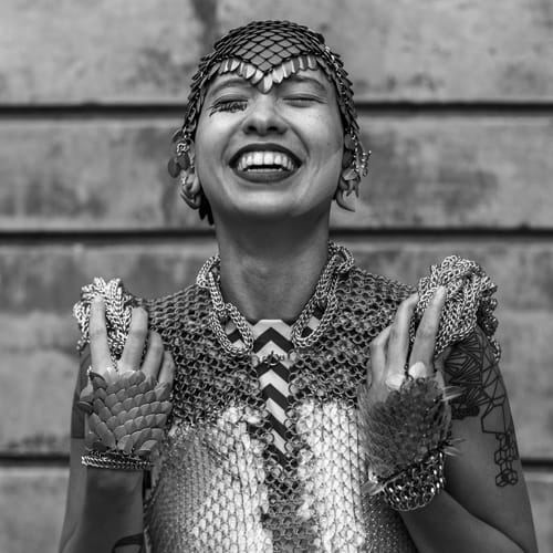 A Filipinx nonbinary person throws back their head and smiles joyously. They have tan skin and wear a reflective headpiece made of metallic scales. They're wearing a radiant chain link top with protruding sculptural shoulders, colorful gloves with metallic scales, and dark lipstick.