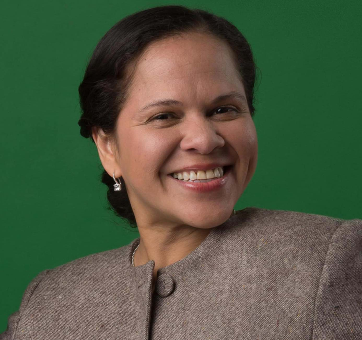 Portrait of Monica Aleman wearing a light brown top against a green background.