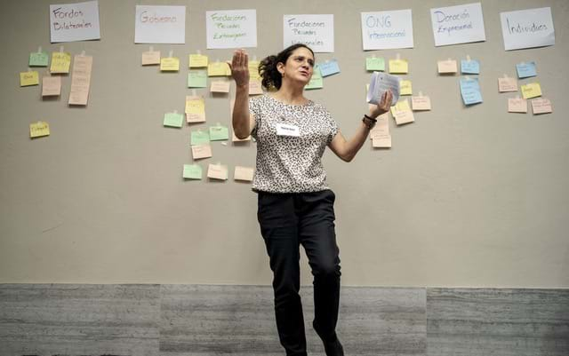 A woman wearing a patterned blouse and black pants stands in front of a wall of sticky notes with her arms open.