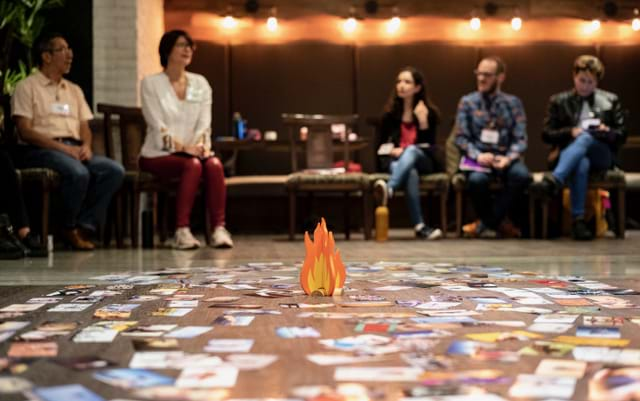 A group of people seated around a cardboard cutout of a campfire surrounded by colorful cards.