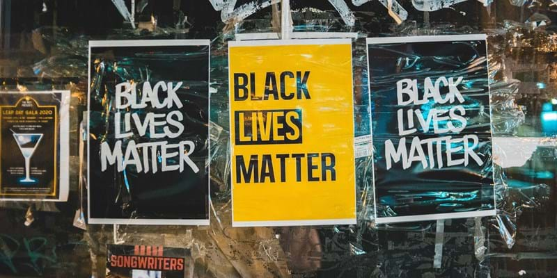 "Black and yellow ""Black Lives Matter"" posters on a graffitied wall."