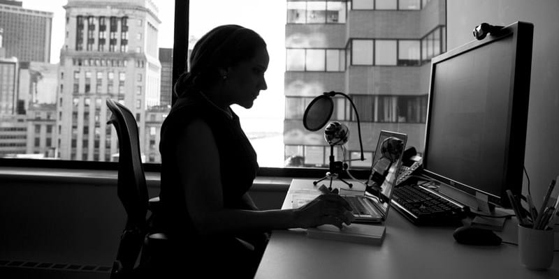 Black and white photo of a woman working in an office, at a computer. City buildings can be seen in the background, through her windows. Photo by #WOCinTech