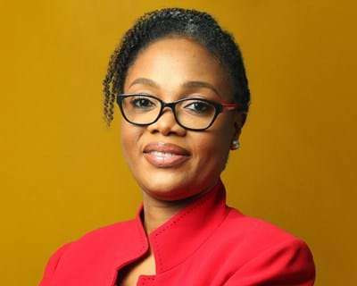 Portrait Olufunke Baruwa wearing a red top and black frame glasses against a mustard yellow background.
