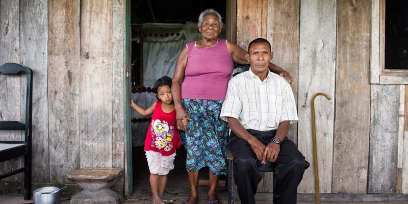 A Honduran man sits in front of a wooden house surrounded by an older woman and a child. There is a cane leaning against the wall behind the man.  Photo: Antonio Busiello