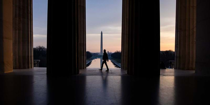 A visitor walks past the mouth of the Lincoln Memorial with the Washington Monument in the distance as the morning light glows in the distance. Photo Samuel Corum/Getty Images