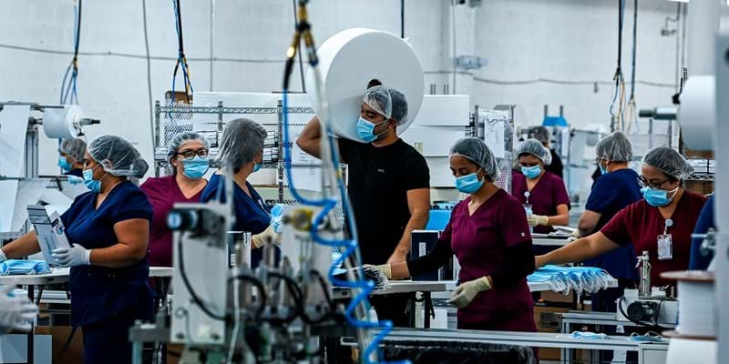 Group of workers wearing hair nets and n95 masks at a medical equipment factory in North Miami, Fla. Photo by CHANDAN KHANNA/AFP via Getty Images